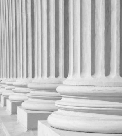 """A row of columns at the entrance to the US Supreme Court in Washington, DC.  Completed in 1935, the US Supreme Court building in Washington, DC, is the first to have been built specifically for the purpose, inspiring Chief Justice Charles Evans Hughes to remark, """"The Republic endures and this is the symbol of its faith.""""  The Court was established in 1789 and initially met in New York City. When the national capital moved to Philadelphia, the Court moved with it, before moving to the permanent capital of Washington, DC, in 1800. Congress lent the Court space in the new Capitol building, and it was to change its meeting place several more times over the next century, even convening for a short period in a private house after the British set fire to the Capitol during the War of 1812.  The classical Corinthian architectural style was chosen to harmonize with nearby congressional buildings, and the scale of the massive marble building reflects the significance and dignity of the judiciary as a co-equal, independent branch of government.  The main entrance is on the west side, facing the Capitol. On either side of the main steps are figures sculpted by James Earle Fraser. On the left is the female Contemplation of Justice. On the right is the male Guardian or Authority of Law. On the architrave above the pediment is the motto """"Equal Justice under Law."""" Capping the entrance is a group representing Liberty Enthroned, guarded by Order and Authority, sculpted by Robert Aitken.  At the west entrance are marble figures sculpted by Hermon A. MacNeil. They represent great law givers Moses, Confucius, and Solon, flanked by Means of Enforcing the Law, Tempering Justice with Mercy, Settlement of Disputes between States, and Maritime and other functions of the Supreme Court. The architrave carries the motto """"Justice the Guardian of Liberty.""""  The interior of the building is equally filled with symbolic ornamentation. The main corridor is known as the Great Hall and contains double """