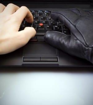 Businessman and hacker hands on laptop keyboard