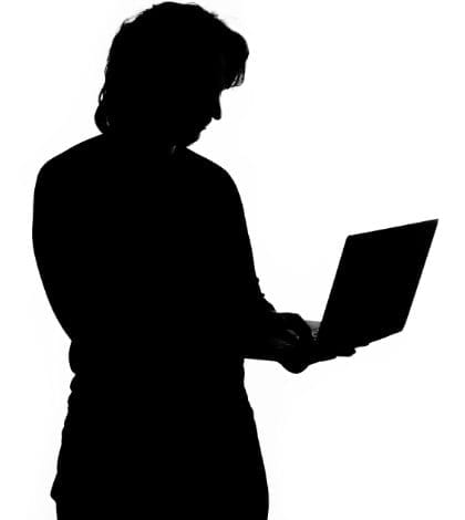 Silhouette of a man holding laptop