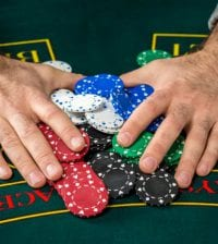 Poker play. Chips on the green table. chips in male hands