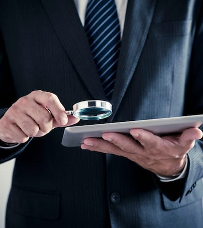 Businessman holding magnifying glass and digital tablet