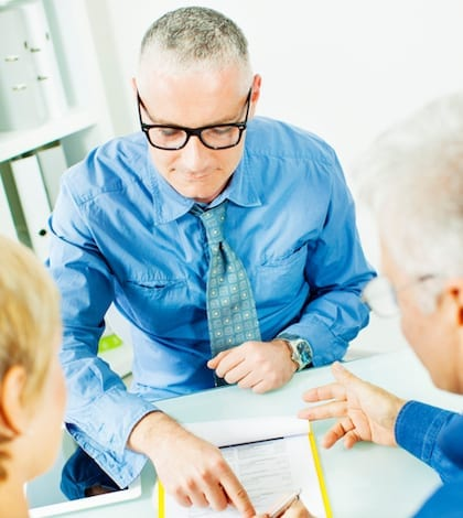 Mature Couple Meeting with Financial Advisor, selective focus to financial advisor pointing to mature woman where to sign contract.