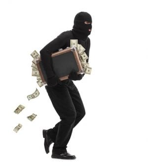 Studio shot of a male burglar with a mask on his head running with a briefcase full of money isolated on white background