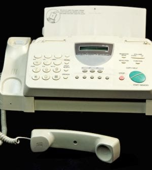 On a well used fax machine with room for copy. On a black background.