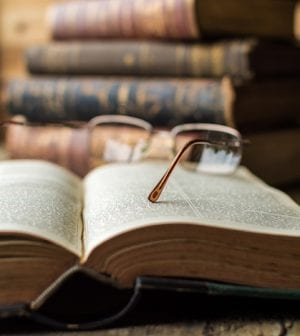 Old Glasses on Open Book, on Wooden Table