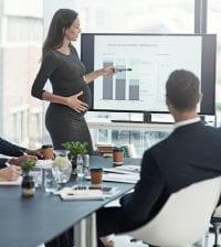Shot of a pregnant businesswoman giving a presentation on a monitor to colleagues in an boardroom