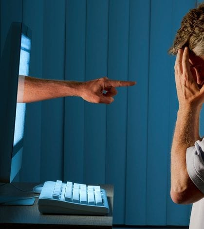 Severely distraught young man sitting in front of a computer with a judgmental hand pointing at him from within the computer monitor which shows the man being either computer bullying bullied or Facebook social media stalking stalked.