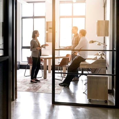 Businesswoman explaining strategy to colleagues seen through glass walls in office. Female professional is giving presentation to executives in board room. All are in meeting.