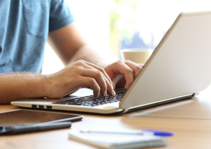 man-hands-typing-on-a-laptop-keyboard-on-a-desk-picture-id865728066