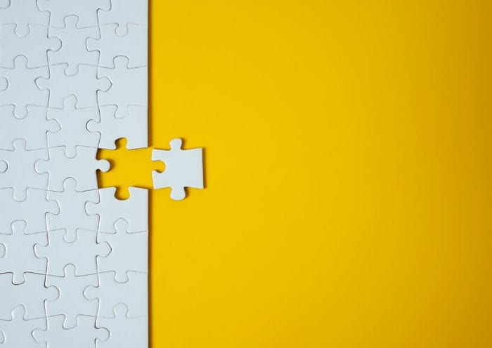 white-jigsaw-puzzle-on-yellow-background-team-business-success-or-picture-id1203219246
