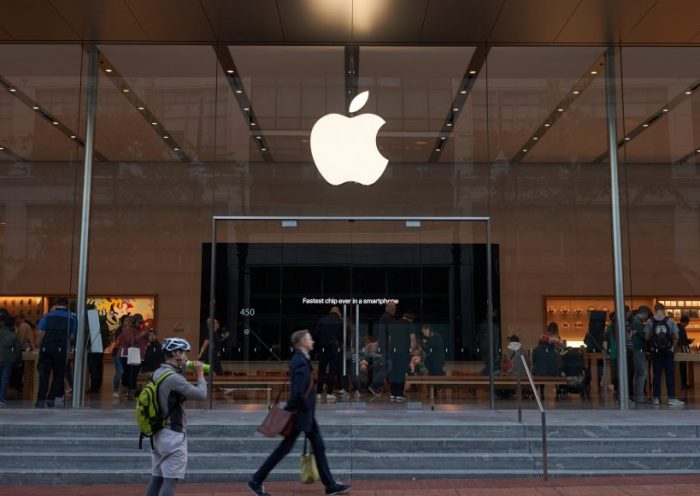 Portland, Oregon, USA - Oct 1, 2019: A man strides past an Apple Store in downtown Portland. The big screen inside is seen advertising Apple's fastest A13 Bionic chips in the new iPhone series.