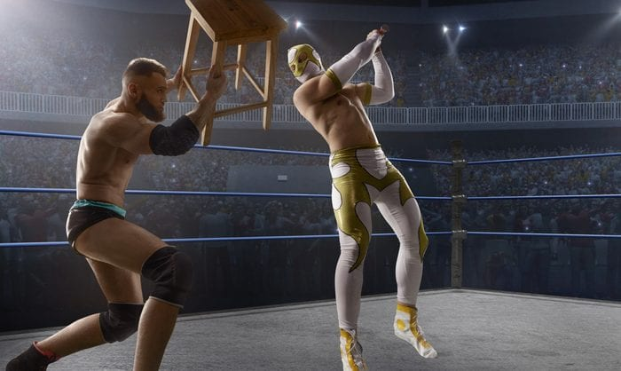 Wrestling show. Two wrestlers in a bright sport clothes and face mask fight in professional ring. One athlete strikes the second man with a chair. The enemy attacks with a bat.