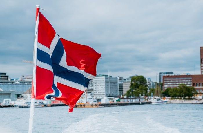 Norway flag on the ferry, view of Oslo city hall, Scandinavia