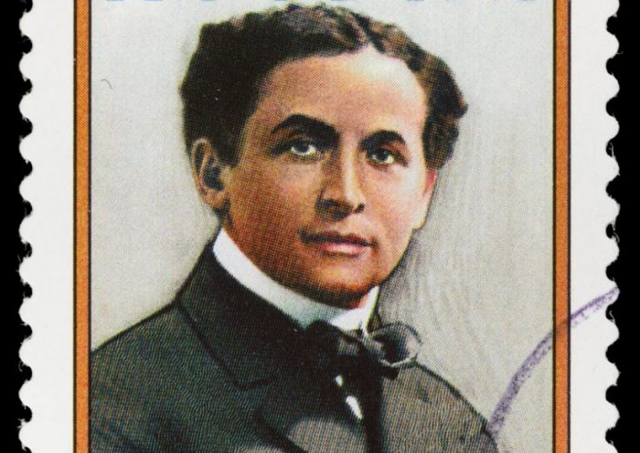 Sacramento, California, USA - March 21, 2012: A 2002 USA postage stamp with a portrait of master magician Harry Houdini (1874-1926). Houdini's magic acts, especially his feats of escape, helped his name become synonymous with the word 'magician' to many Americans of that era.