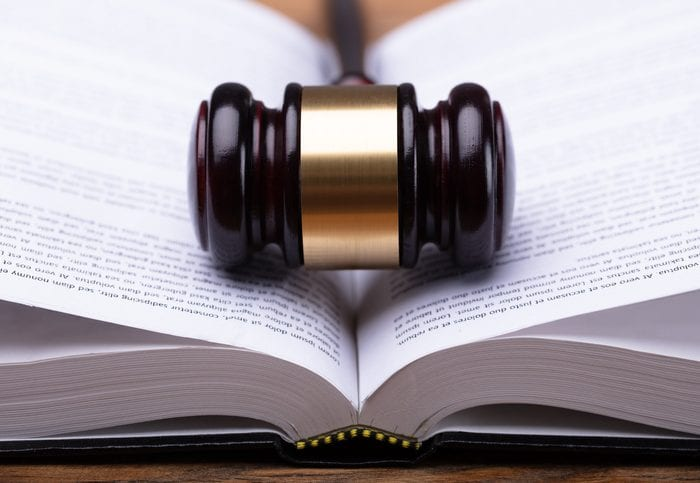 Close-up Of Wooden Gavel And Open Law Book