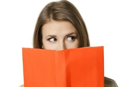 Closeup of young woman peeking over the edge of the opened book, looking to the side at blank copy space, over white background