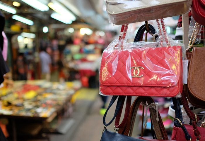 Kuala Lumpur, Malaysia - August 19, 2015: Some fake bags on sale in China Town market in Kuala Lumpur. In this area it is full of small shops selling a plenty of counterfeit merchandise illegally. This area is popular among tourist, and sometimes they are not aware that buying these fake goods is illegal and may lead to problems at the customs.