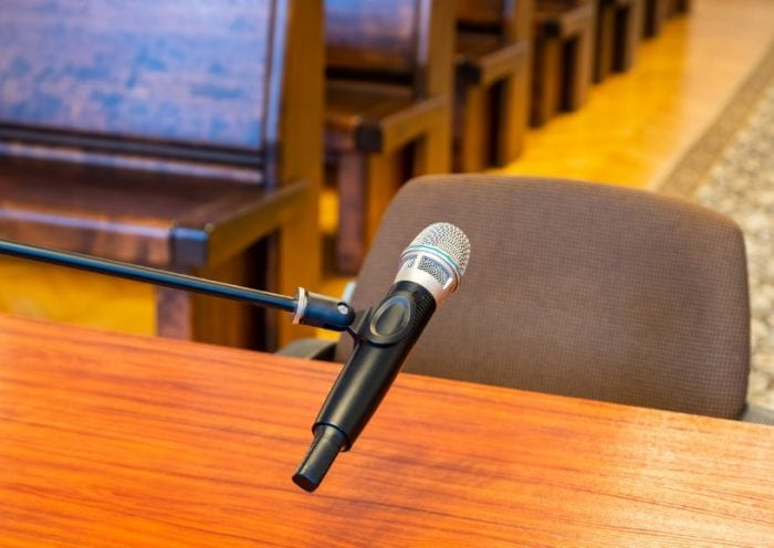closeup-of-microphone-in-the-courthouse-justice-system-witness-picture-id1299975522