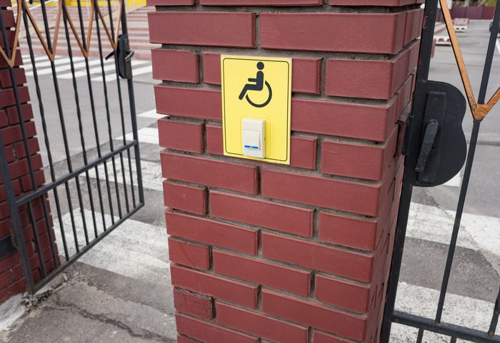Assistance button for disabled people at the entrance of the iron gate. A disabled sign on a wall, concept image.