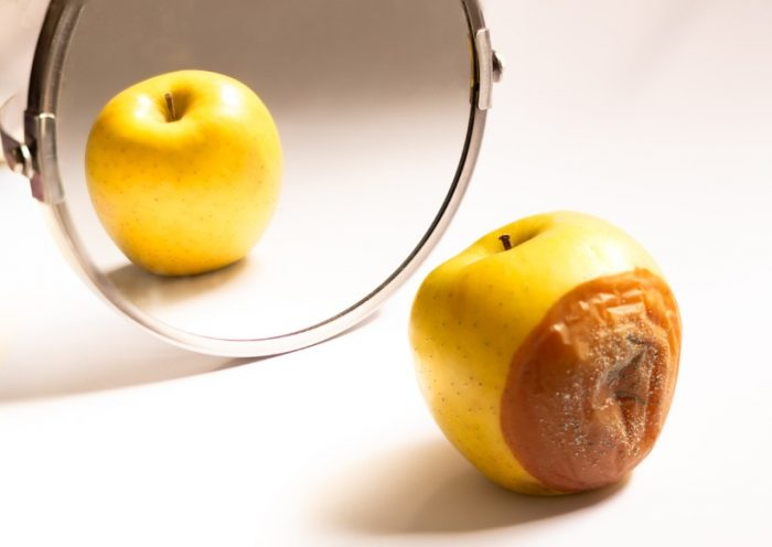 apple-in-good-condition-looking-at-itself-in-the-mirror-while-its-is-picture-id1225356870