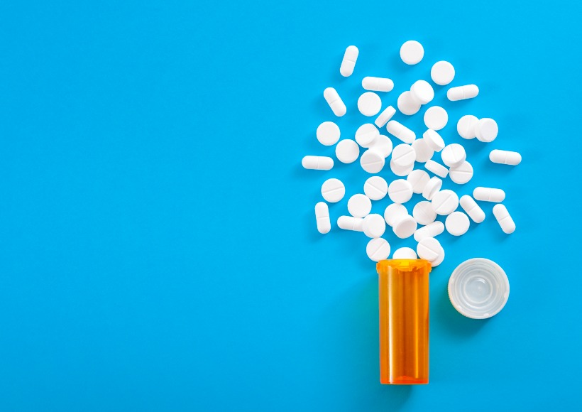pills-falling-from-pill-bottle-on-blue-background-with-copyspace-picture-id1035982466