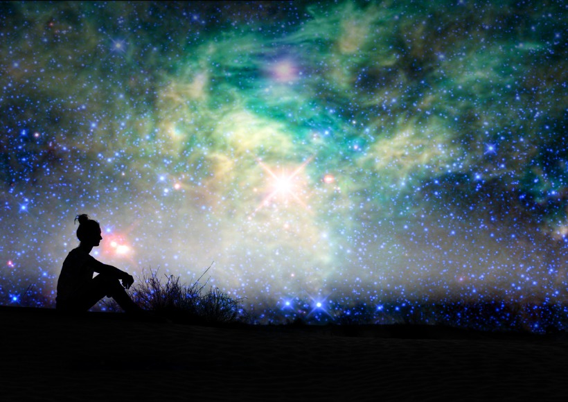 silhouette-of-a-woman-sitting-outside-starry-night-background-picture-id619750134