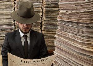 retro man reading newspaper in newspaper storage room