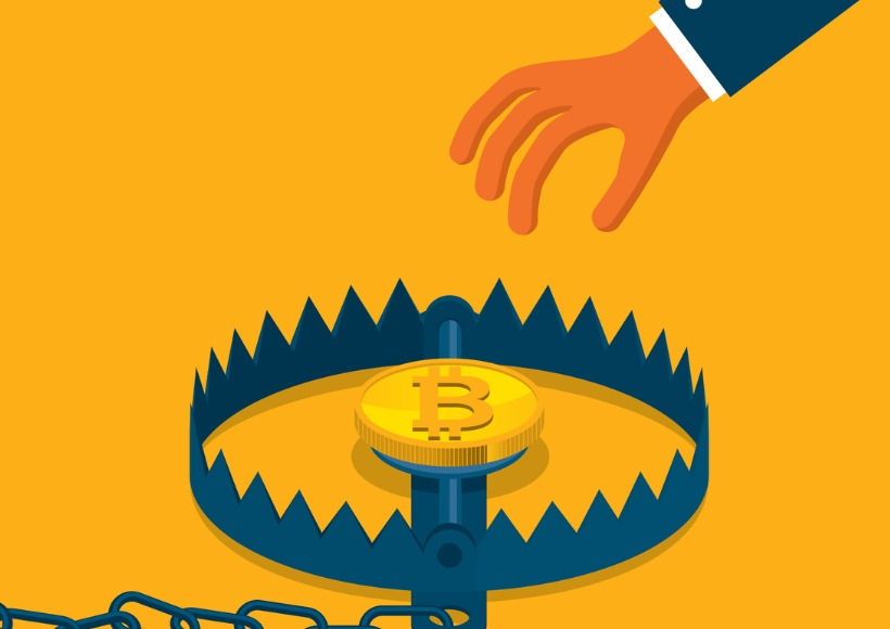 Hand reaches towards bitcoin sitting in a trap