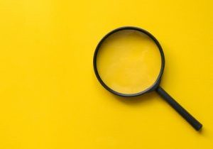 close-up-magnifier-glass-on-yellow-background-for-design-on-web-page-picture-id1133860020